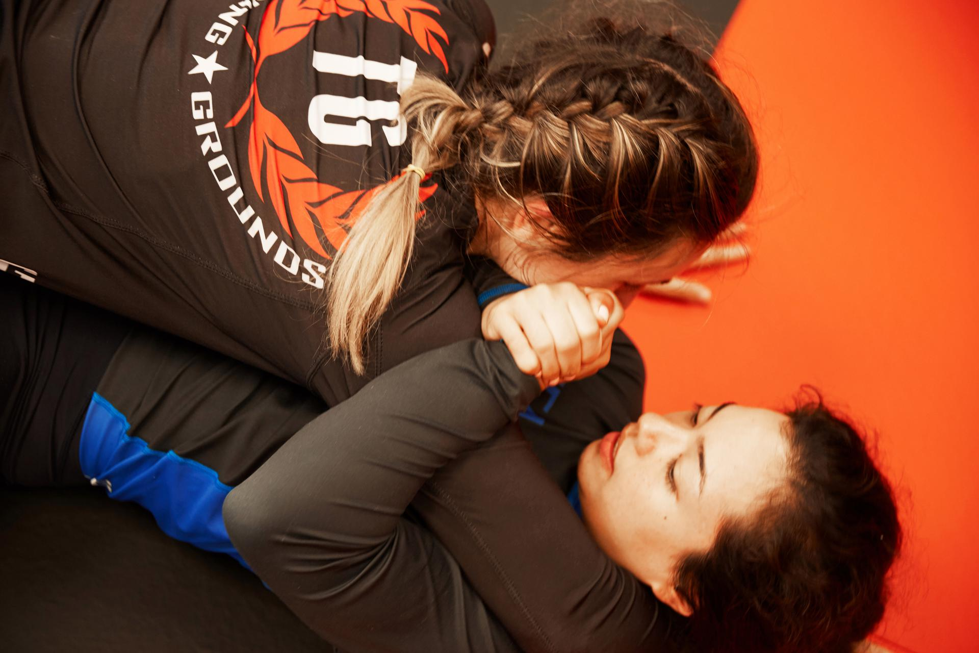 two young women in a girls mma class at training grounds practicing an armbar