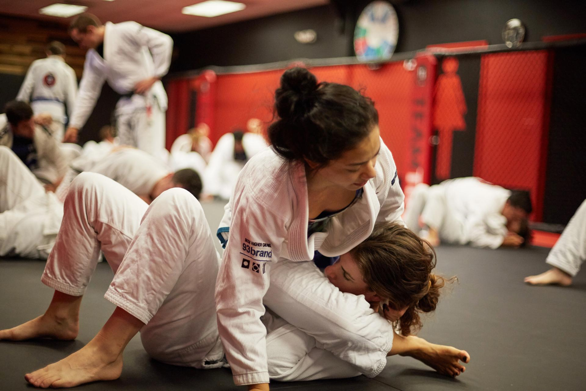 a girls bjj class in full swing as two girl practice a straight armlock