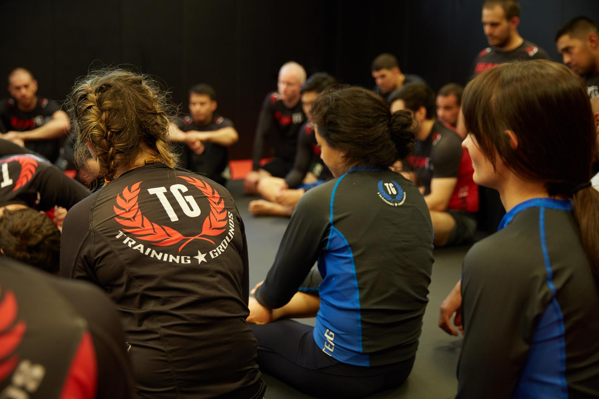 a shot from the back as a group of females watch the bjj class