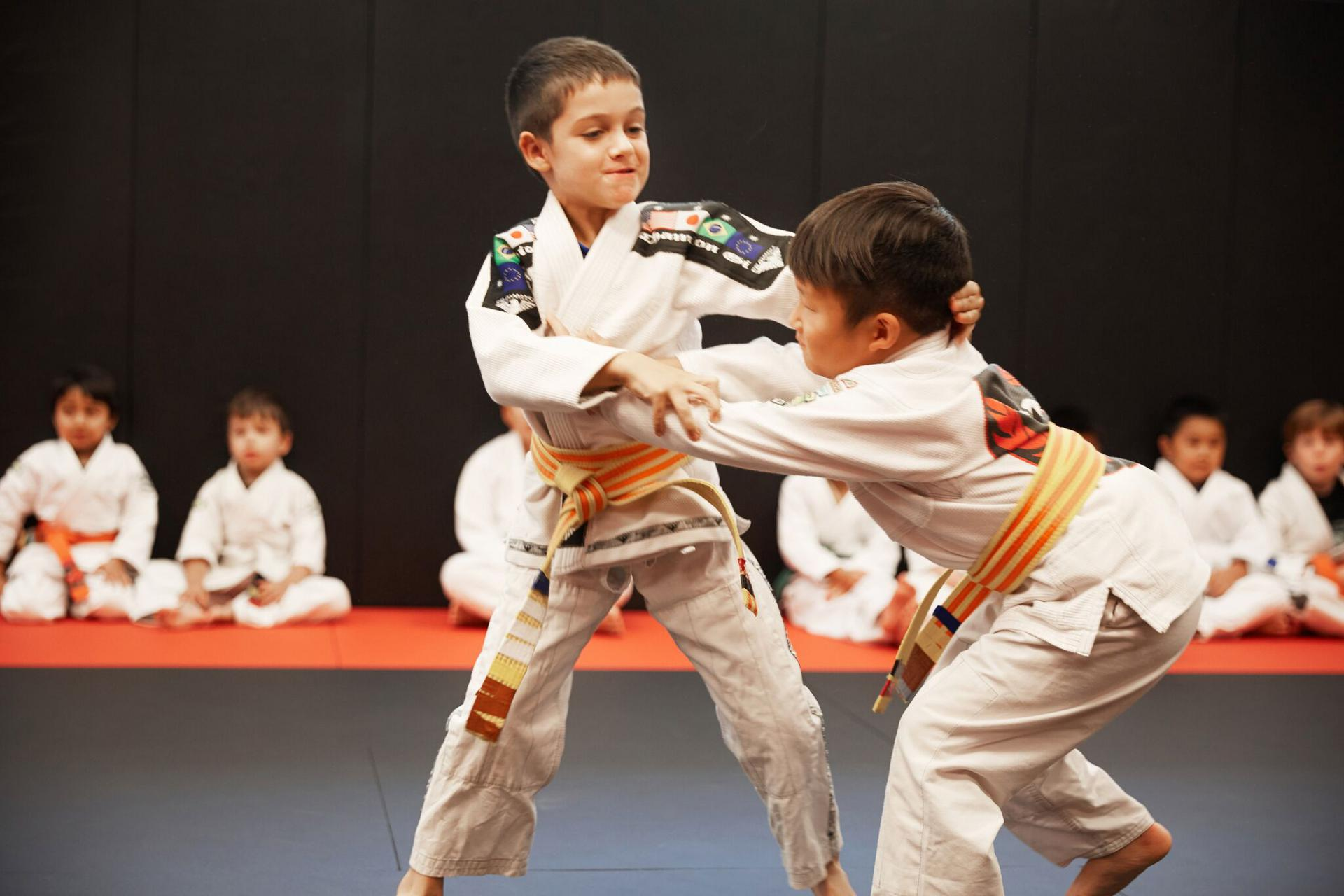 a confident kid doing a match with another child in a kids martial arts class focused on bullying