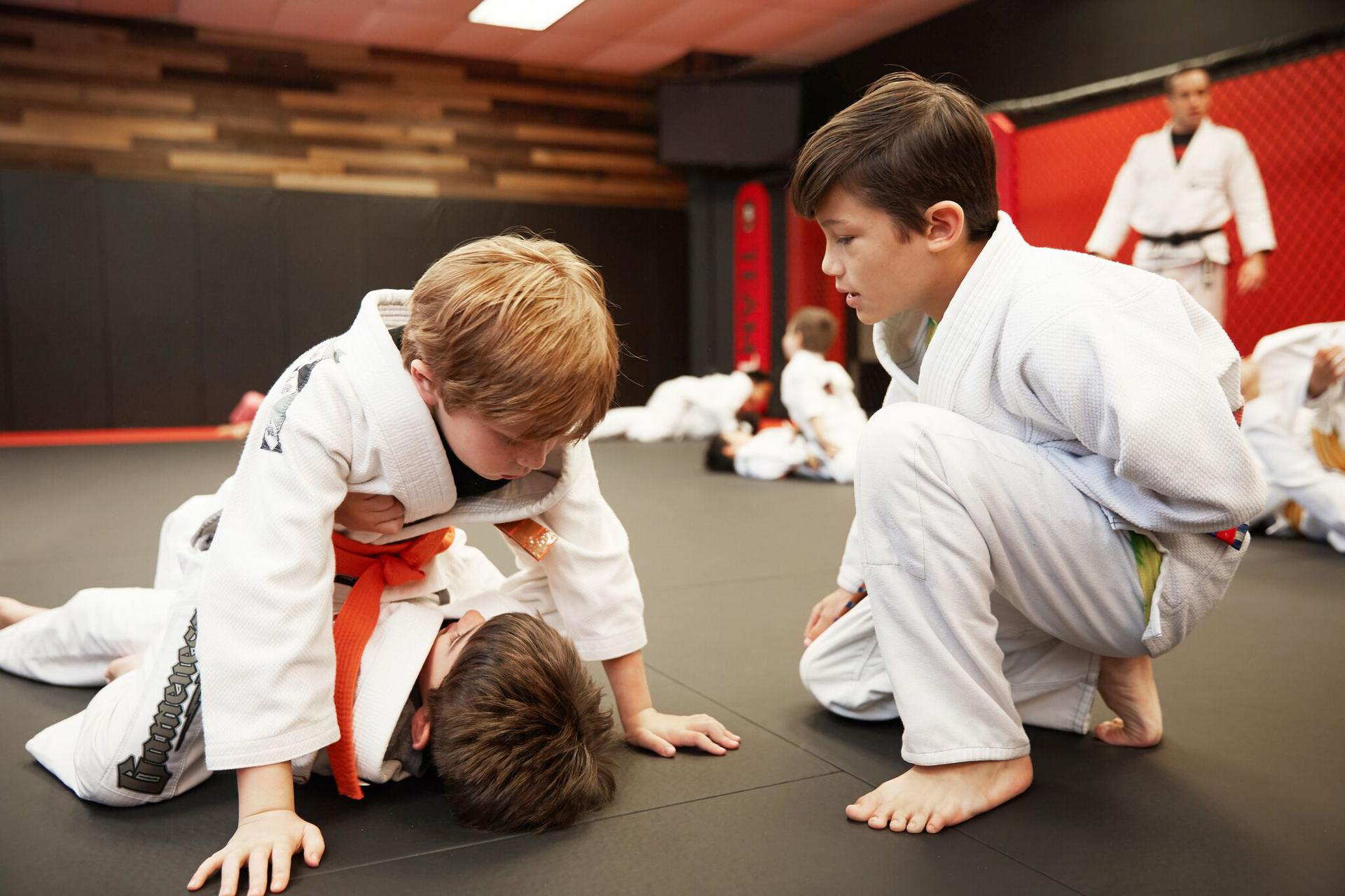 an older child coaching two younger children in a martial arts class in westwood