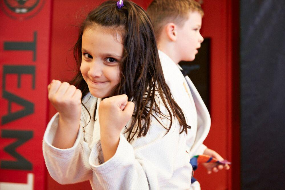 a girl with her fists up looking tough with her martial art uniform on