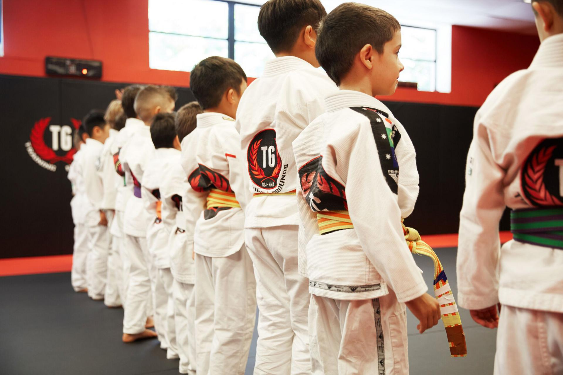 a line of children with their backs turned at the start of a kids martial arts class