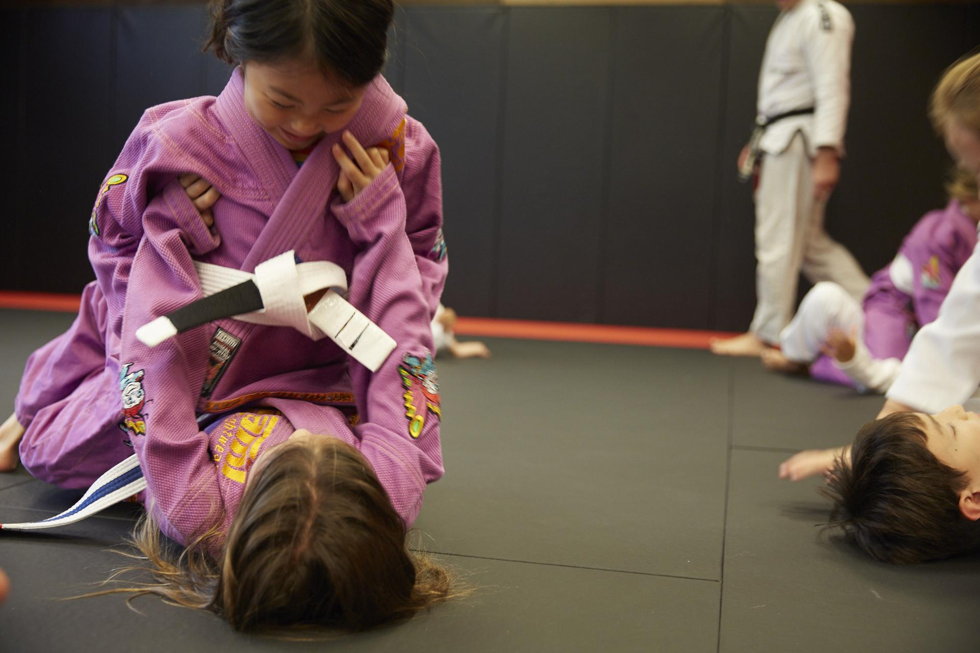 two girls smiling at each other a training grounds kids martial arts class
