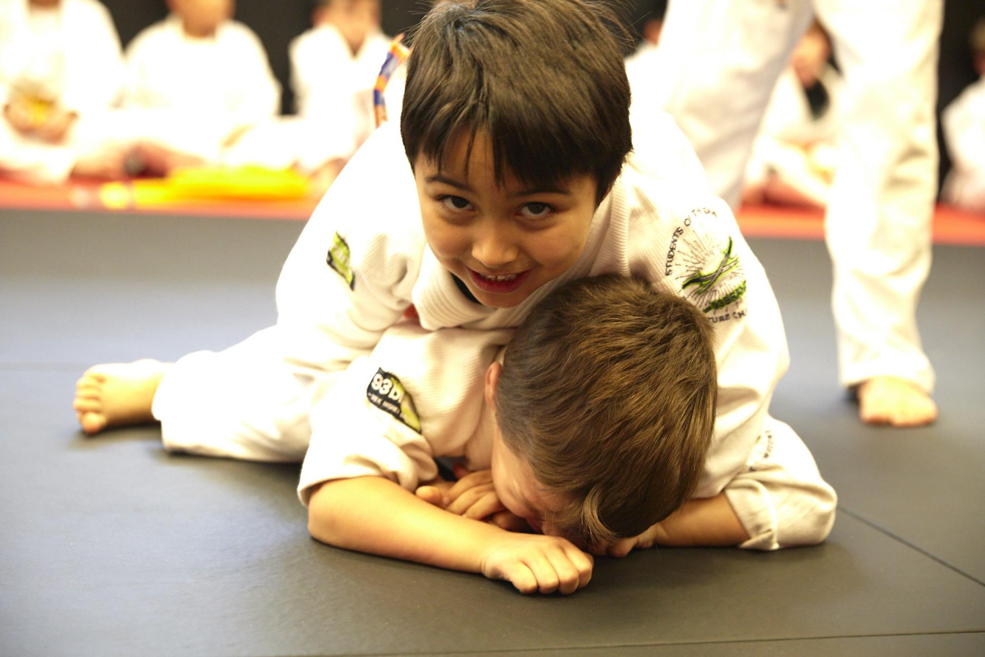 a boy smiling and feeling very confident with his performance in a brazilian jiu jitsu match at training grounds