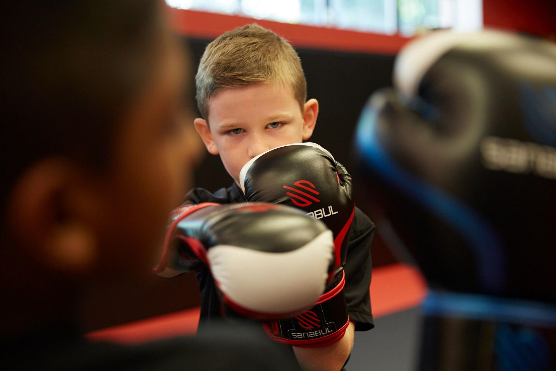 a child with gloves on throwing a punch in a martial art class