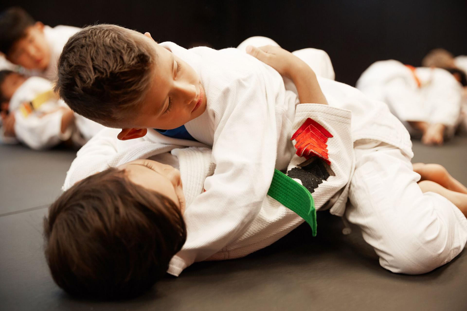 kids stopping to listen to the martial arts instructor during class